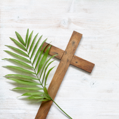Palm frond and cross on wooden background
